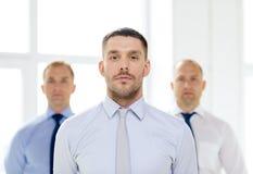 Σοβαρός επιχειρηματίας στην αρχή με την ομάδα στην πλάτη Στοκ φωτογραφία με δικαίωμα ελεύθερης χρήσης