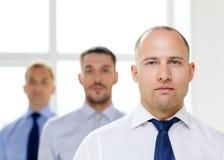 Σοβαρός επιχειρηματίας στην αρχή με την ομάδα στην πλάτη Στοκ Φωτογραφίες