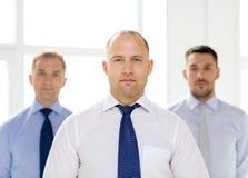Σοβαρός επιχειρηματίας στην αρχή με την ομάδα στην πλάτη Στοκ Εικόνες