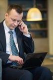 Σοβαρός επιχειρηματίας στη συνεδρίαση κοστουμιών και δεσμών με ένα lap-top Στοκ εικόνες με δικαίωμα ελεύθερης χρήσης