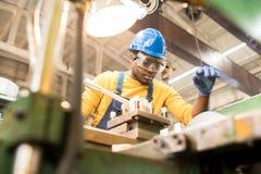 Σοβαρός εργαζόμενος που επισκευάζει τη μηχανή κατασκευής στοκ φωτογραφίες