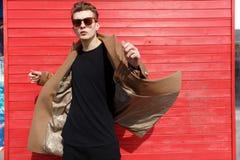 Σοβαρός ελκυστικός νεαρός άνδρας στα γυαλιά ηλίου και το τρέξιμο παλτών Στοκ Εικόνες