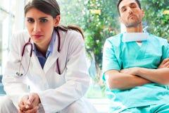 Σοβαρός θηλυκός γιατρός με το συνάδελφο στο νοσοκομείο Στοκ Εικόνες
