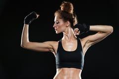 Σοβαρός θηλυκός μαχητής που παρουσιάζει δικέφαλους μυς της Στοκ Εικόνες