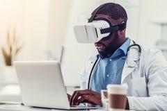 Σοβαρός ιατρικός εργαζόμενος στα προστατευτικά δίοπτρα VR που λειτουργούν στο lap-top Στοκ Εικόνα