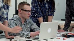 Σοβαρός διευθυντής στα γυαλιά που εξετάζουν τον υπολογιστή και που μιλούν στην ομάδα του απόθεμα βίντεο