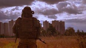 Σοβαρός καυκάσιος ισχυρός στρατιωτικός στην κάλυψη, εξετάζοντας αυθεντικά το αυτόματο όπλο και τις στροφές εκμετάλλευσης καμερών απόθεμα βίντεο