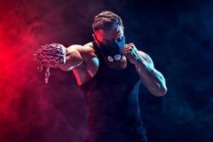 Σοβαρός μυϊκός μαχητής που κάνει τη διάτρηση με τις αλυσίδες που πλέκονται πέρα από την πυγμή του στοκ εικόνα με δικαίωμα ελεύθερης χρήσης