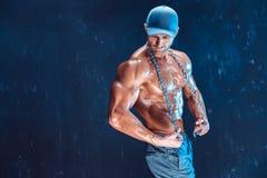 Σοβαρός μυϊκός μαχητής στην ΚΑΠ με τις αλυσίδες πέρα από το λαιμό του στον καπνό Στοκ Φωτογραφία