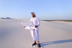 Σοβαρός νέος αραβικός επιχειρηματίας που εξετάζει το σχέδιο κατασκευής, ST Στοκ Εικόνες