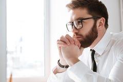 Σοβαρός νέος επιχειρηματίας που εξετάζει τον υπολογιστή Στοκ Φωτογραφία
