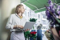 Σοβαρός νέος εργαζόμενος που εξετάζει κατά μέρος το παράθυρο στοκ φωτογραφία με δικαίωμα ελεύθερης χρήσης