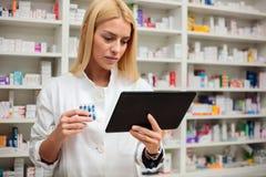 Σοβαρός νέος θηλυκός φαρμακοποιός που χρησιμοποιεί μια ταμπλέτα σε ένα φαρμακείο στοκ εικόνα