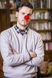 Σοβαρός νεαρός άνδρας με την κόκκινη μύτη κλόουν Στοκ φωτογραφία με δικαίωμα ελεύθερης χρήσης