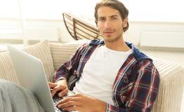 Σοβαρός νεαρός άνδρας με το lap-top Στοκ Φωτογραφία