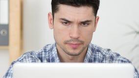 Σοβαρός νεαρός άνδρας που εργάζεται στο lap-top, μπροστινή άποψη Στοκ εικόνα με δικαίωμα ελεύθερης χρήσης