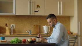 Σοβαρός νεαρός άνδρας που χρησιμοποιεί την ψηφιακή συνεδρίαση υπολογιστών ταμπλετών στην κουζίνα ενώ έχει το πρόγευμα το πρωί Στοκ Εικόνες