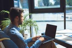 σοβαρός νεαρός άνδρας που χρησιμοποιεί το lap-top με την κενή οθόνη Στοκ φωτογραφία με δικαίωμα ελεύθερης χρήσης