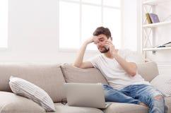 Σοβαρός νεαρός άνδρας στο σπίτι με το lap-top και κινητός Στοκ Εικόνες