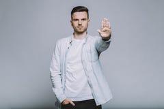 Σοβαρός νεαρός άνδρας με τη γενειάδα σε ένα άσπρο πουκάμισο που στέκεται στο απομονωμένο υπόβαθρο Στοκ φωτογραφία με δικαίωμα ελεύθερης χρήσης