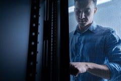 Σοβαρός νεαρός άνδρας που εργάζεται στο δωμάτιο κεντρικών υπολογιστών Στοκ Εικόνα