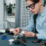 Σοβαρός νεαρός άνδρας που καθορίζει το κινητό τηλέφωνο ελεύθερου χώρου Στοκ φωτογραφία με δικαίωμα ελεύθερης χρήσης