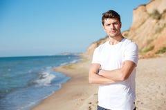 Σοβαρός νεαρός άνδρας που στέκεται στην παραλία Στοκ Εικόνες