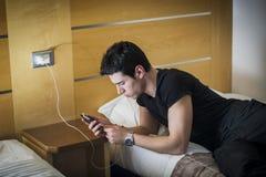 Σοβαρός νεαρός άνδρας που συνδέει ένα τηλέφωνο με έναν φορτιστή Στοκ Εικόνα