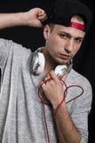 Σοβαρός νεαρός άνδρας σε μια ΚΑΠ και με τα ακουστικά γύρω από το λαιμό του Στοκ Φωτογραφία