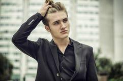 Σοβαρός ξανθός νεαρός άνδρας στα τζιν και το σακάκι, που κάθονται υπαίθρια Στοκ εικόνες με δικαίωμα ελεύθερης χρήσης