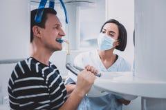 Σοβαρός οδοντίατρος brunette που εξετάζει τον ασθενή της στοκ φωτογραφίες