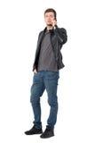 Σοβαρός περιστασιακός νεαρός άνδρας στα τζιν και το σακάκι δέρματος που μιλά στο κινητό τηλέφωνο Στοκ Φωτογραφία