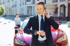 Σοβαρός πολυάσχολος επιχειρηματίας που εξετάζει το ρολόι του Στοκ φωτογραφίες με δικαίωμα ελεύθερης χρήσης