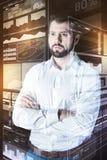 Σοβαρός προγραμματιστής που στέκεται με τα όπλα του που διασχίζονται και που σκέφτεται Στοκ Φωτογραφία