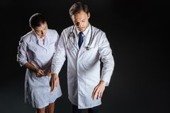 Σοβαρός συγκεντρωμένος γιατρός που μένει και που εξηγεί Στοκ Φωτογραφίες