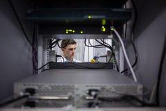 Σοβαρός τεχνικός που χρησιμοποιεί την ψηφιακή συσκευή ανάλυσης καλωδίων στον κεντρικό υπολογιστή Στοκ φωτογραφίες με δικαίωμα ελεύθερης χρήσης