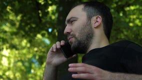 Σοβαρός τύπος που μιλά στο τηλέφωνο στο πάρκο φιλμ μικρού μήκους