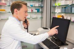 Σοβαρός φαρμακοποιός στο τηλέφωνο που χρησιμοποιεί τον υπολογιστή στοκ φωτογραφία