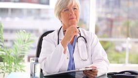 Σοβαρός ώριμος γιατρός που γράφει στην περιοχή αποκομμάτων της απόθεμα βίντεο