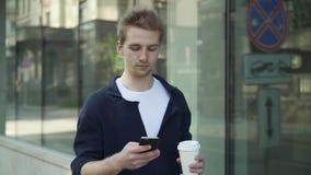 Σοβαρό άτομο με το περπάτημα και τον Ιστό καφέ που κάνει σερφ στην οδό απόθεμα βίντεο
