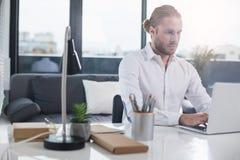 Σοβαρό άτομο που εξετάζει τον υπολογιστή με την προσοχή Στοκ εικόνα με δικαίωμα ελεύθερης χρήσης