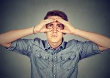 Σοβαρό άτομο που κοιτάζει μέσω των χεριών που διαμορφώνονται ως διόπτρες Στοκ Φωτογραφίες