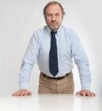 Σοβαρό άτομο που κλίνει σε ένα γραφείο Στοκ Εικόνες