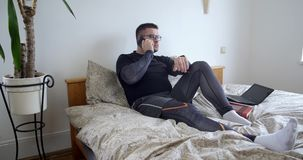 Σοβαρό άτομο που μιλά στο τηλέφωνο στο σπίτι στην κρεβατοκάμαρα απόθεμα βίντεο