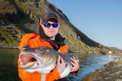 Σοβαρό άτομο στον ψαρά γυαλιών που κρατά έναν βακαλάο ogromnyu ψαριών Στοκ Φωτογραφίες