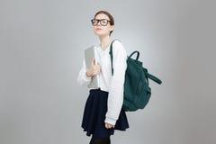 Σοβαρό έφηβη στα γυαλιά με το lap-top εκμετάλλευσης σακιδίων πλάτης Στοκ φωτογραφία με δικαίωμα ελεύθερης χρήσης