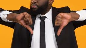 Σοβαρό αφροαμερικανός επιχειρησιακό άτομο που παρουσιάζει αντίχειρες κάτω, θέση εργασίας απέχθειας απόθεμα βίντεο