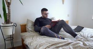 Σοβαρό βιβλίο ανάγνωσης ατόμων στο σπίτι στην κρεβατοκάμαρα φιλμ μικρού μήκους