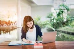 Σοβαρό γράψιμο σπουδαστών νέων κοριτσιών με το βιβλίο και το lap-top σχολικών φακέλλων στοκ φωτογραφία με δικαίωμα ελεύθερης χρήσης