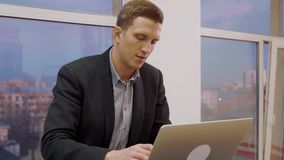 Σοβαρό επιχειρησιακό άτομο που εργάζεται στο φορητό προσωπικό υπολογιστή στο υπόβαθρο παραθύρων στην αρχή απόθεμα βίντεο